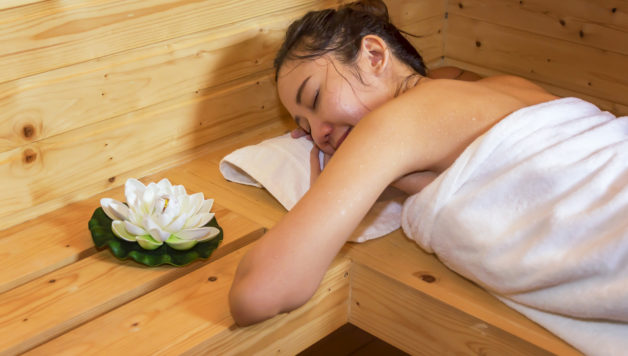 Beautiful Young asian girl sleeping relax, lying in sauna cabin in spa sauna room.