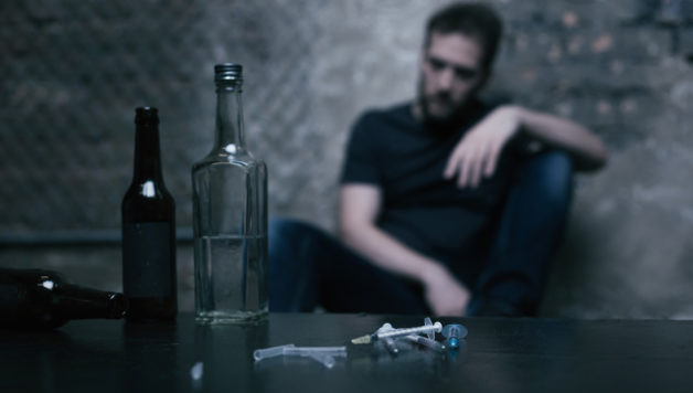 Treating loneliness of my soul. Different full big bottles located on the table in the garage next to the used syringes while junkie sitting in the background