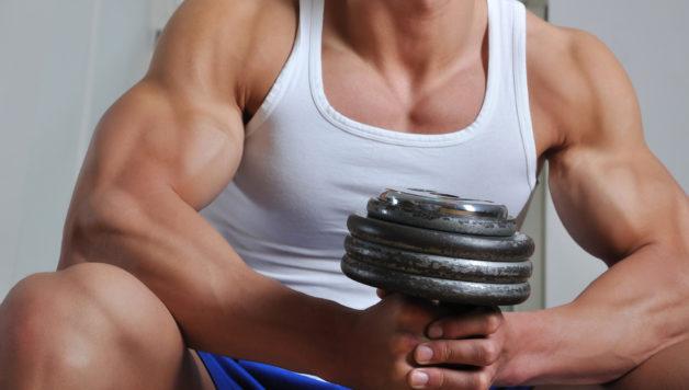 Powerful muscular man lifting weight